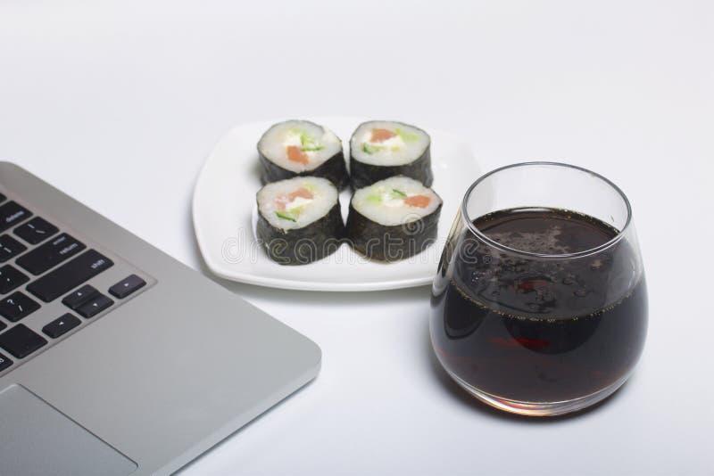 Bier en sushi Tribune dichtbij laptop Rust met voedsel en gadgets stock foto