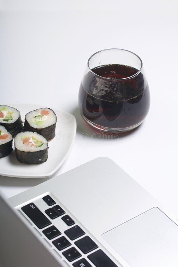 Bier en sushi Tribune dichtbij laptop Rust met voedsel en gadgets royalty-vrije stock fotografie
