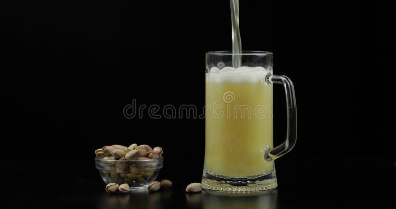 Bier gie?t in Glas auf schwarzem Hintergrund Sch?ssel Pistazien stockbild