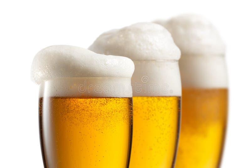 Bier in glazen die op wit worden geïsoleerd stock afbeelding