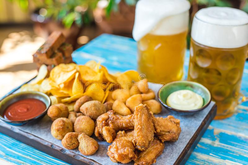 Bier in glazen met snacks, kippengoudklompjes, spaanders en sausen stock foto's