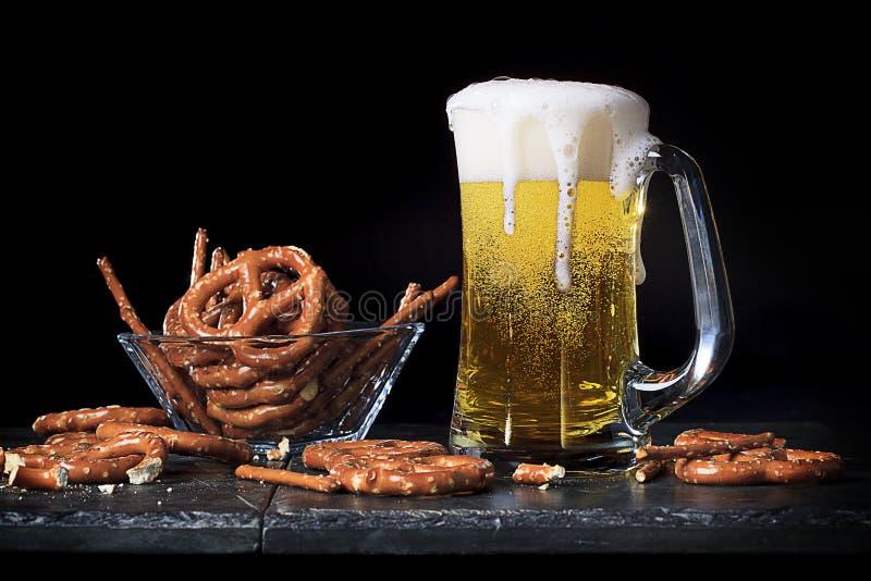 Bier im Glasbecher mit Brezeln stockbild