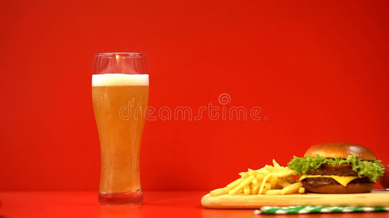 Bier met schuim en hamburger op rode achtergrond, koolhydraten en vettig voedsel stock foto