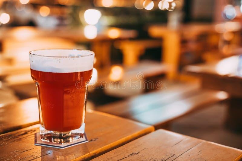 Bier mit Fruchtgeschmack oder Fruchtsaft auf Restauranttabelle mit Kopienraum auf Unschärfe bokeh Hintergrund Feierkonzept des gl lizenzfreie stockfotografie