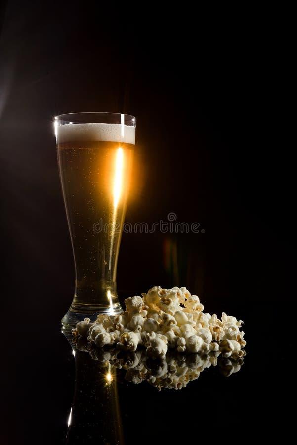 Bier mit Schaum und Popcorn stockfoto