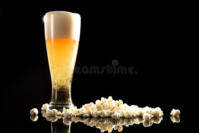 Bier mit Schaum und Popcorn stockbilder
