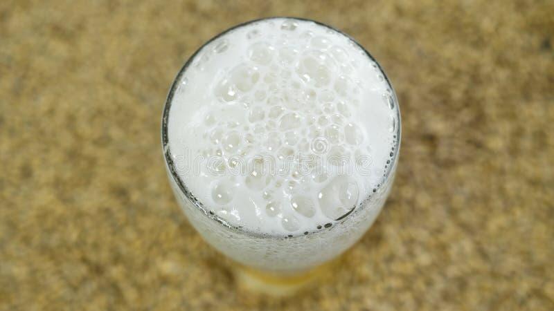 Bier mit Schaum vom natürlichen Malz und von den Hopfen, gekocht in einer privaten Brauerei vor dem hintergrund des Kornes, Drauf lizenzfreies stockbild