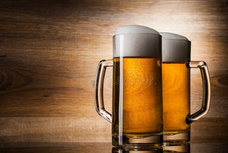 Bier mit zwei Gläsern auf hölzernem Hintergrund lizenzfreies stockfoto