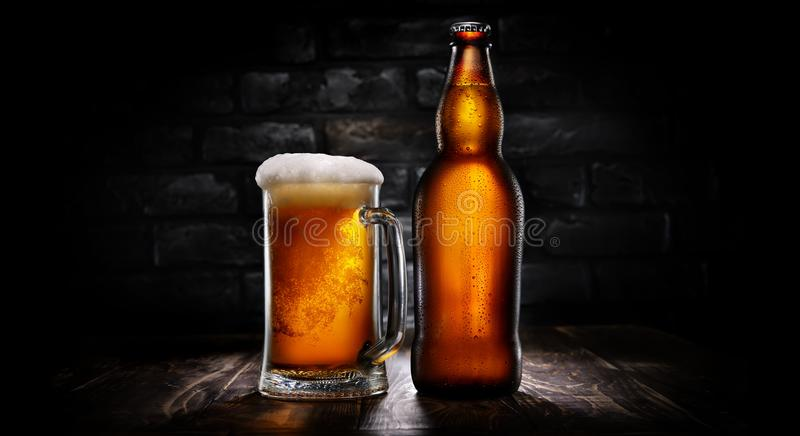 Bier in mok en fles op zwarte royalty-vrije stock afbeelding