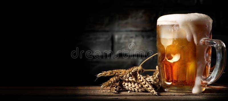 Bier in mok op lijst stock fotografie