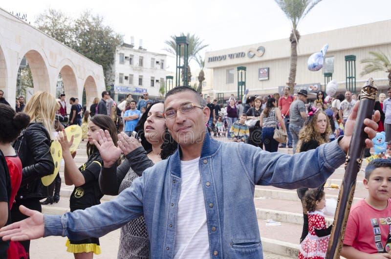 Bier-Sheva, ISRAËL - Maart 5, 2015: De man in glazen met een stuk speelgoed staaf in van hem dient de straat in - Purim stock afbeeldingen
