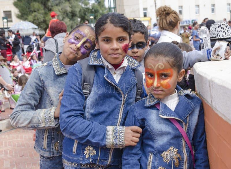 Bier-Sheva, ISRAËL - Maart 5, 2015: Drie tieners en een jongen in denim kleden zich met Carnaval-make-up op hun gezichten Purim stock foto