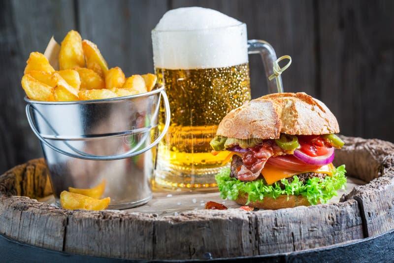 Bier und geschmackvoller Burger mit Gemüse, Rindfleisch und Pepperonis stockfotos
