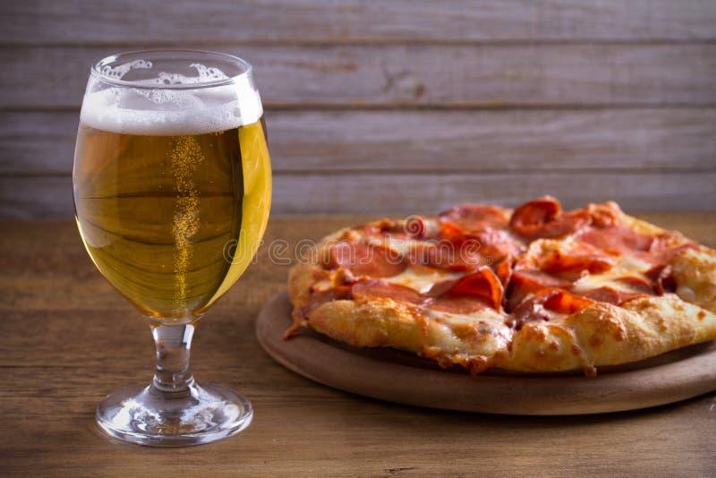 Bier und Pepperonipizza auf Holztisch Glas Bier Ale- und Lebensmittelkonzept lizenzfreie stockfotos