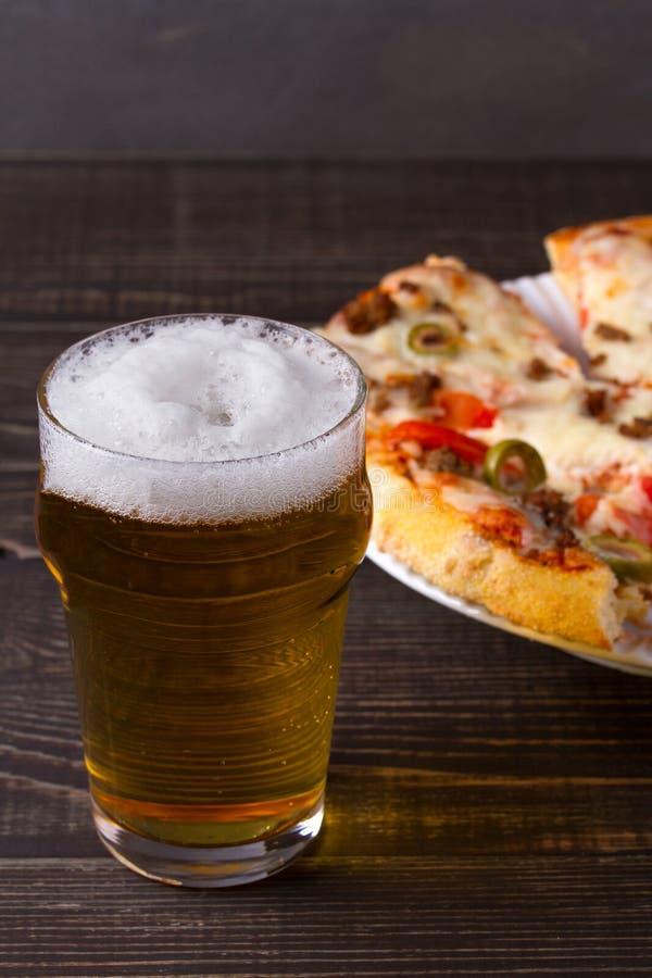 Bier und Pizza auf dunklem hölzernem Hintergrund Ale und Lebensmittel stockbild
