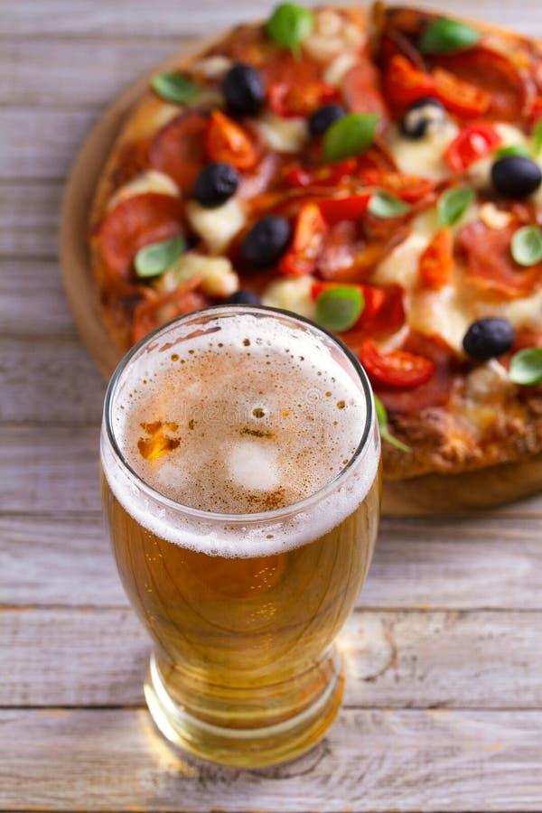 Bier und Pizza auf hölzerner Platte Ale und Imbiss horizontal lizenzfreies stockfoto