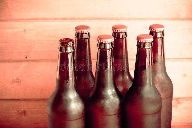Bierflaschen auf rustikalem hölzernem Hintergrund Abbildung der roten Lilie lizenzfreie stockfotos