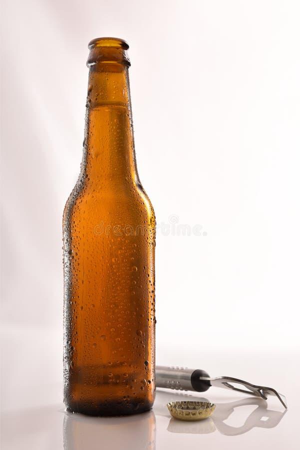 Bierfles open op de flesopener van de glaslijst stock afbeelding