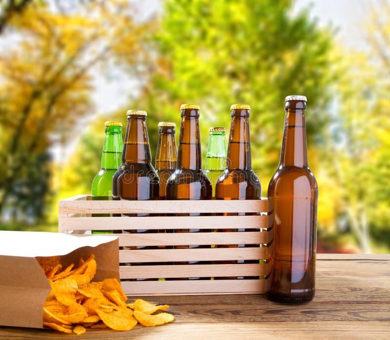 Bierflessen en chips op houten lijst met vaag park op achtergrond, gekleurd fles, voedsel en drankconcept, selectieve FO royalty-vrije stock afbeelding