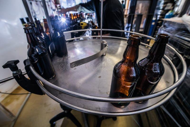 Bierflessen op transportband stock afbeeldingen