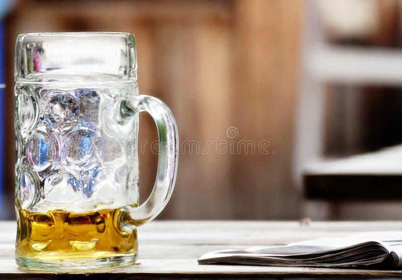Bierglas fast emprty auf einer Tabelle nahe einer Zeitschrift lizenzfreies stockbild