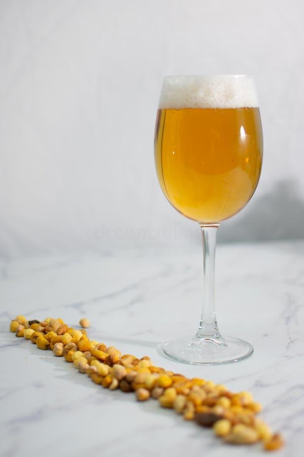 Bierglas mit Imbiss von Nüssen auf weißem Hintergrund stockbilder