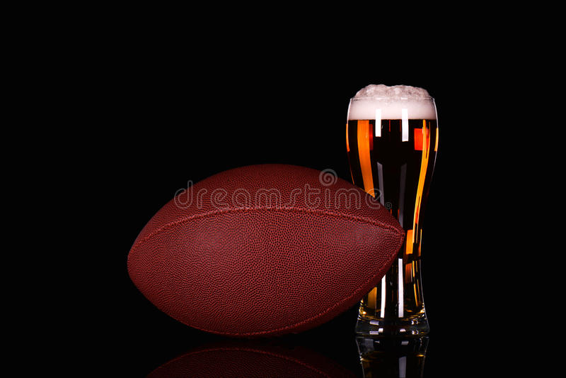 Bierglas mit Schaum des dunklen Bieres und Ball des amerikanischen Fußballs auf schwarzem Hintergrund lizenzfreie stockbilder