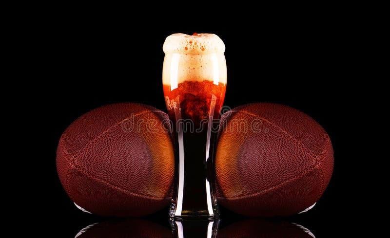Bierglas mit Schaum des dunklen Bieres und Ball des amerikanischen Fußballs auf schwarzem Hintergrund lizenzfreies stockbild