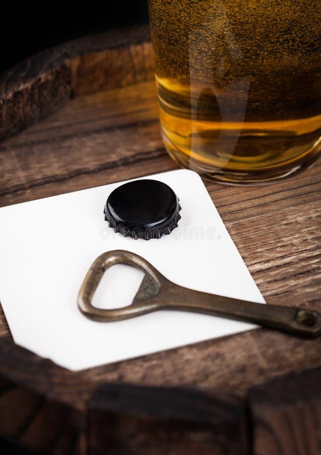 Bierküstenmotorschiff mit Flaschenspitze und Öffner und Glas Bier auf hölzernes Fass lizenzfreies stockfoto