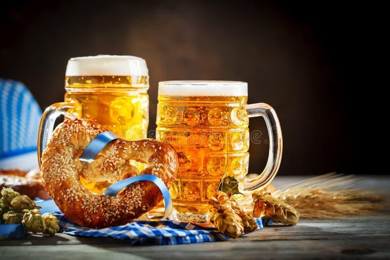 Bierkrüge und Brezeln auf einem Holztisch Oktoberfest Bierfestival stockfotos
