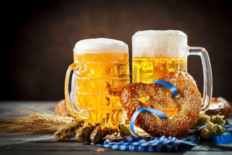 Bierkrüge und Brezeln auf einem Holztisch Oktoberfest Bierfestival lizenzfreies stockfoto
