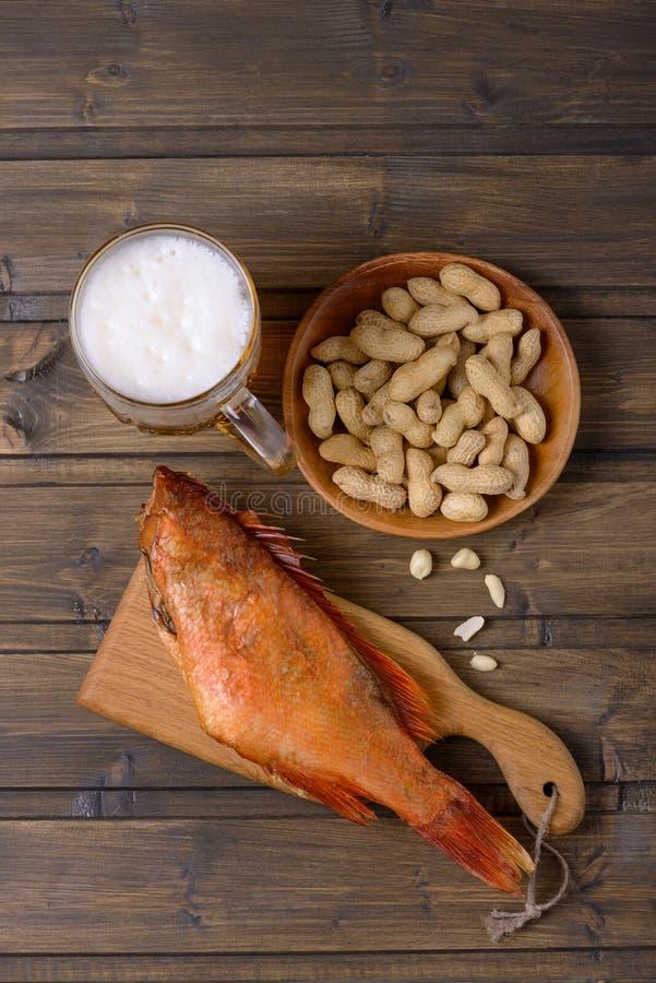 Bierkrug und Fische mit Erdnüssen auf Holztisch lizenzfreie stockfotos