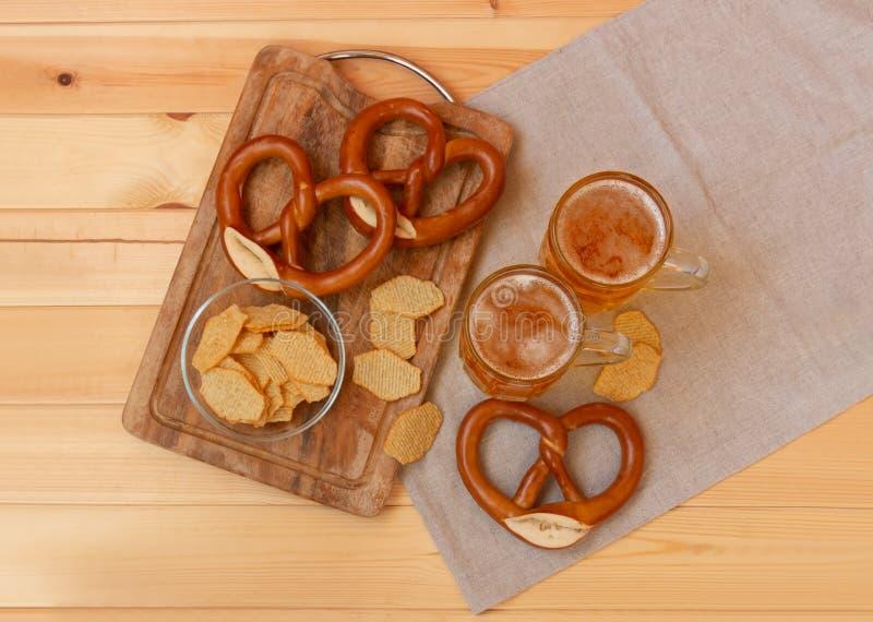Biermokken, chips en pretzels op houten lijst stock afbeelding