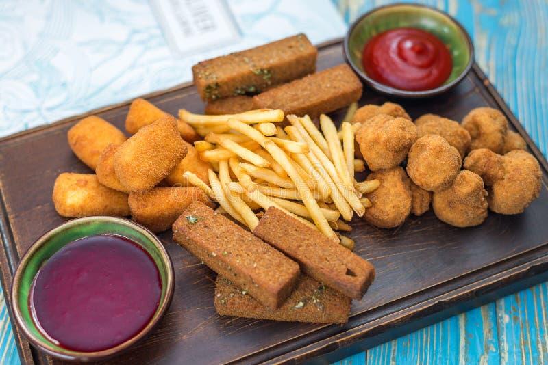 Bierplaat met aardappelgebraden gerechten, kaas, paddestoelen en sausen royalty-vrije stock fotografie