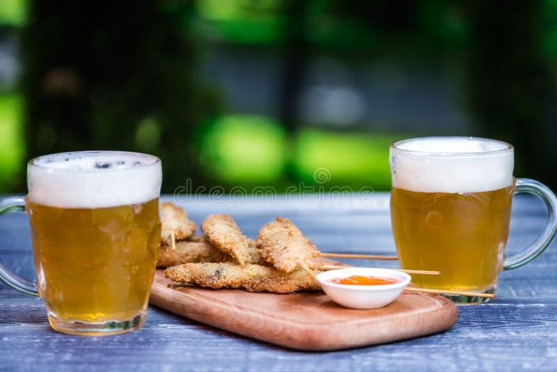 Biersn?cke eingestellt H?hnerfl?gel auf St?cken und zwei Bechern Bier Auf dem Schneidebrett und gr?nen dem Sommerhintergrund lizenzfreies stockbild