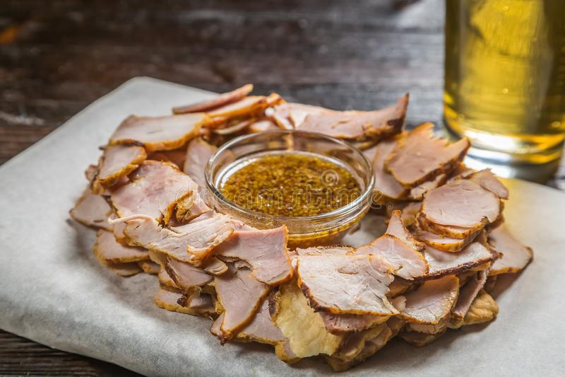 Biersnack von dünn geschnittenen Stücken Fleisch mit einer Soße des körnigen Senfes auf dem Brett für die Archivierung wird mit e lizenzfreie stockbilder