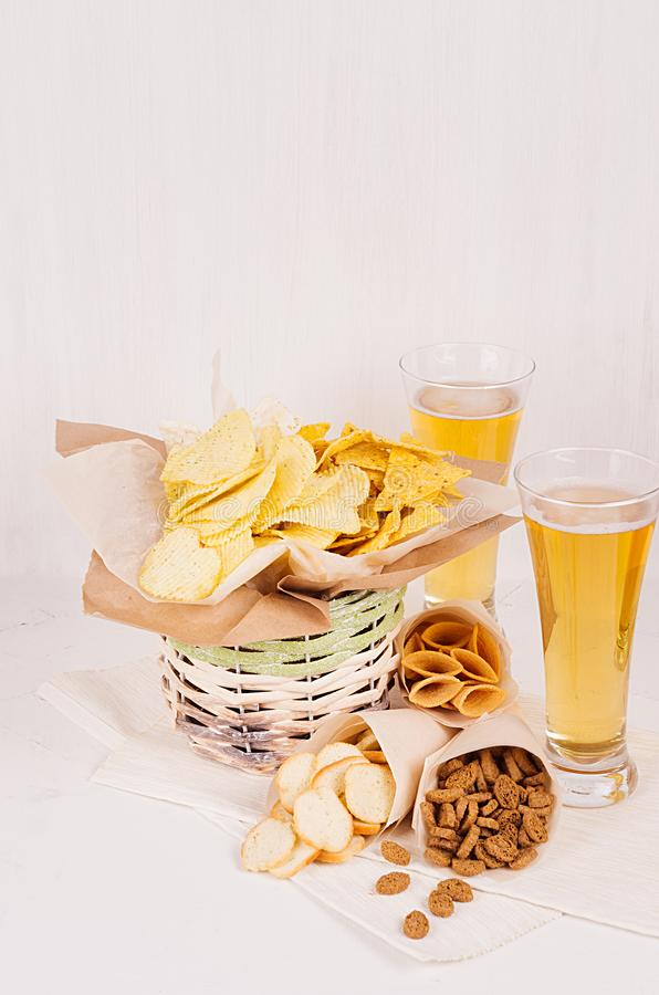 Biersnacks in ambachtdocument en twee lagerbierbier in glas op zachte verse houten lijst stock fotografie