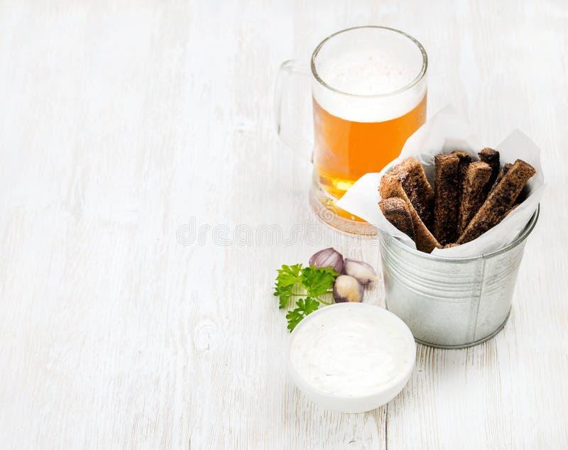 Biersnacksatz Halbes Liter von Pilsener in den Glasbecher- und Roggenbrotcroutons mit Frischkäse des Knoblauchs sauce über dem ge lizenzfreies stockbild