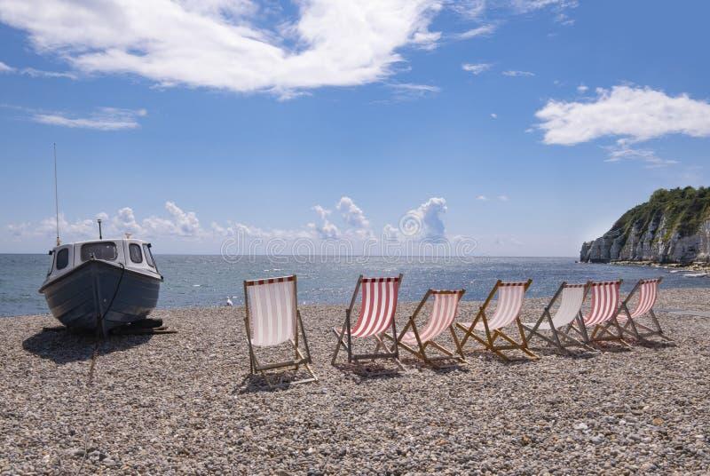 Bierstrand, Devon, Großbritannien streifte deckchairs auf Pebble Beach stockfotografie