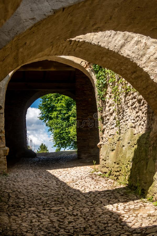 Arches over the cobblestone entrance to the Saxon UNESCO World Heritage Site of Biertan Fortified Church. Sibiu County, Romania. The Biertan fortified church is stock image