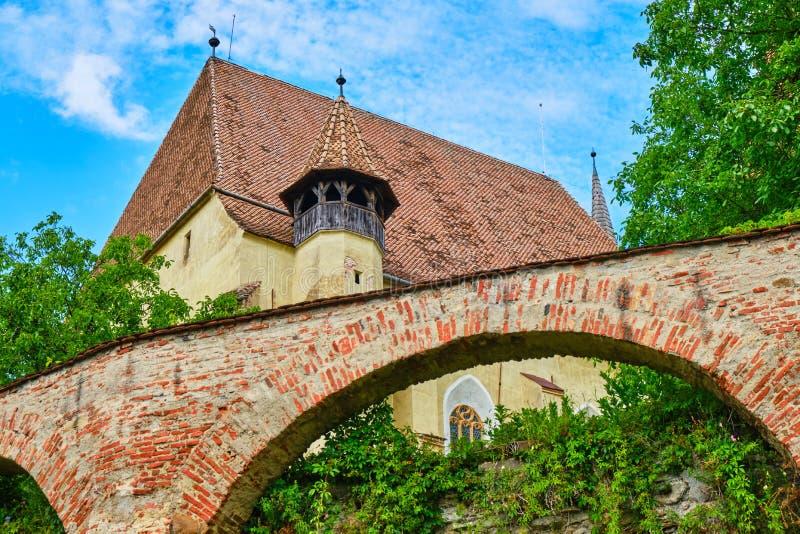 Biertan-Wehrkirche - Außenansicht der Ziegelstein gewölbten Wand, des Teils des Kirchturms und des Dachs kleines blaues Auto auf  stockfotos