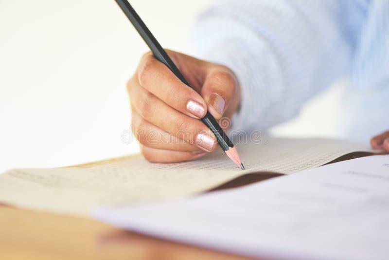 Bierze egzaminowi definitywnego szkoły średniej student uniwersytetu mienia ołówek pisze na papierowym odpowiedzi prześcieradle - zdjęcia stock