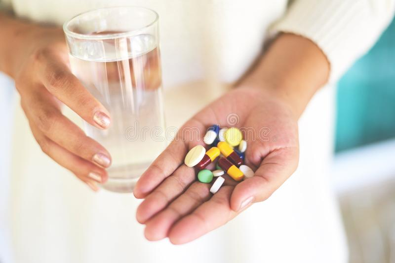 Bierze medycyny opiekę zdrowotną i zaludnia pojęcie Wiele wielo- kolor pigułki w ręki kobiecie i brać z wodnym szkłem - obraz stock
