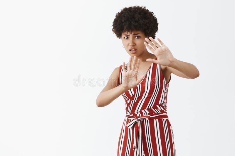 Bierze mnie zdala od ja Niepewna nierada i nieszcz??liwa ciemnosk?ra kobieta z afro fryzur? w modnym stroju d?wiganiu zdjęcie stock