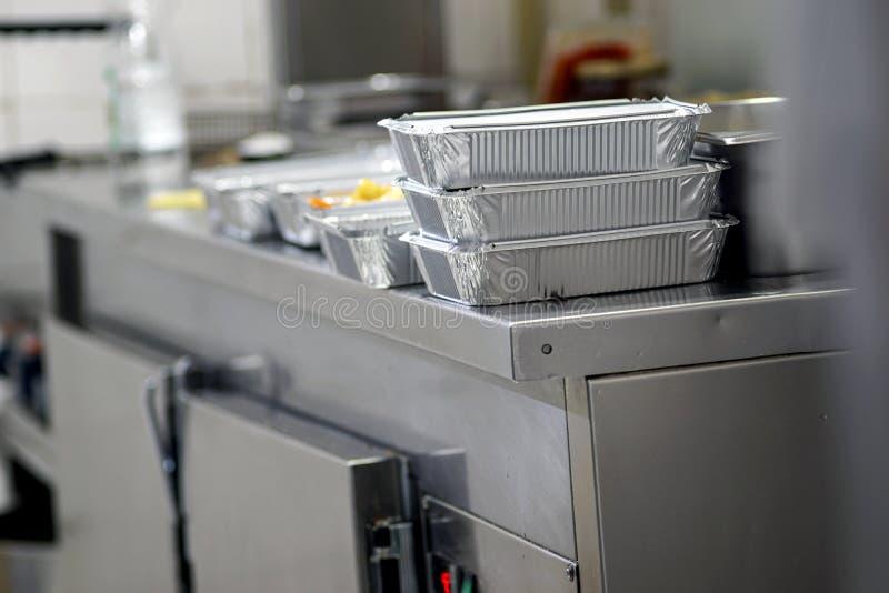 Bierze oddalonego jedzenie w foliowych pudełkach w Chińskiej restauracyjnej kuchni fotografia royalty free