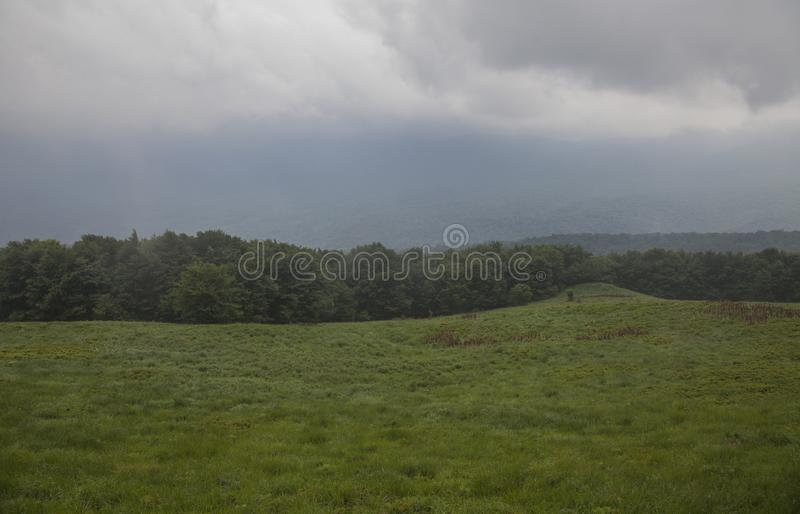 Bieszczady Mountains, south Poland, Europe - green grass and cloudy skies; summer 2018. This image shows a view of hills, green meadows and cloudy skies in royalty free stock image