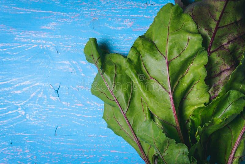 Bietenbovenkanten op oude blauwe houten lijst De ruimte van het exemplaar Gezond voedsel Rauwe groenten stock foto's
