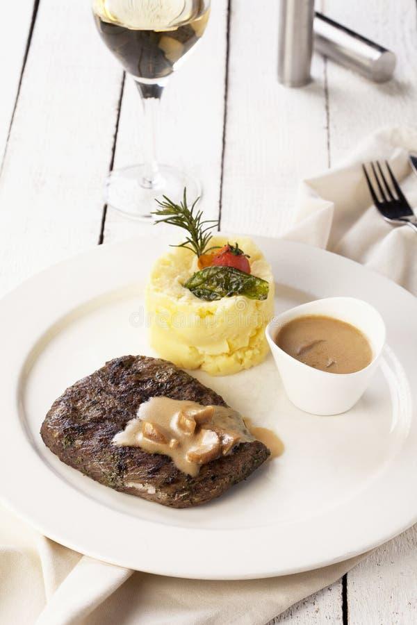 Bife com batata de erva-benta e vinho branco em um fundo branco imagem de stock royalty free