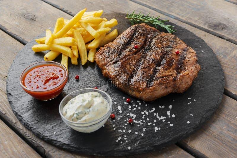 Bife com batatas fritas e molho imagens de stock royalty free