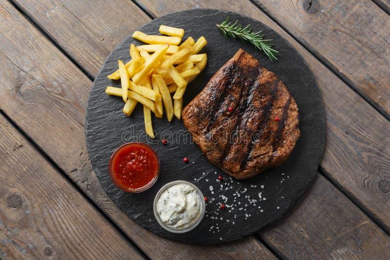 Bife com batatas fritas e molho fotografia de stock royalty free